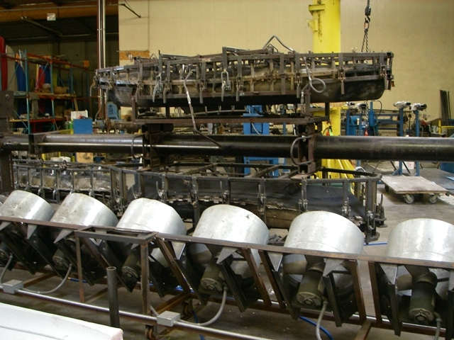 A rotational mold (top) is cooled by a bank of fans before pulling the hull out.