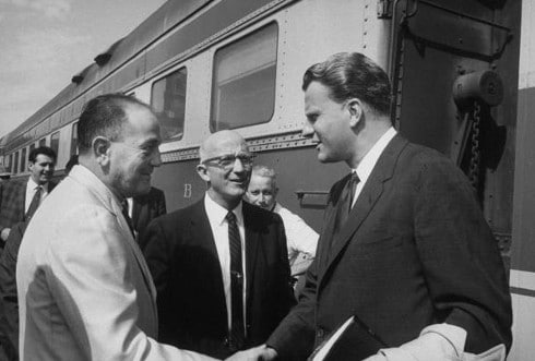 Vintage important businessmen shaking hands meeting outside train.