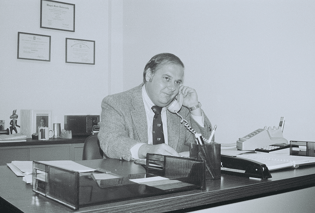 vintage businessman at desk in suit talking on phone
