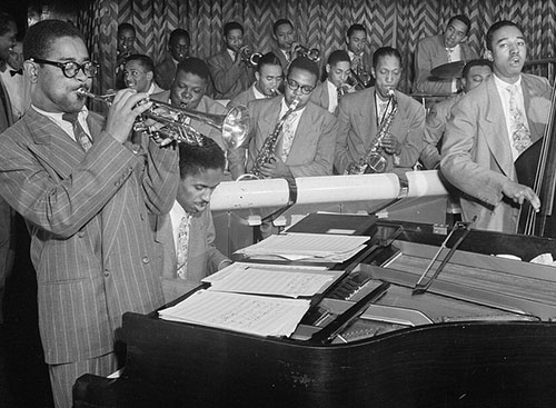 Dizzy Gillespie playing trumpet with jazz band behind.
