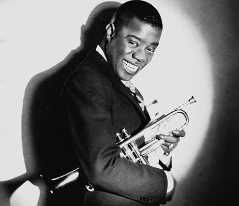 Young louis armstrong smiling big smile with trumpet.