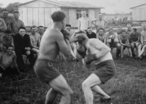 vintage men boxing in grass yard field with onlooking action shot