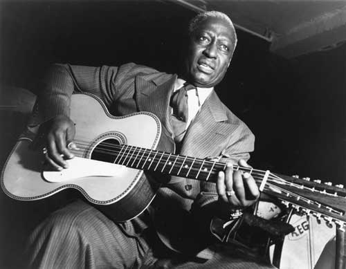 Lead belly jazz musician guitarist playing guitar.