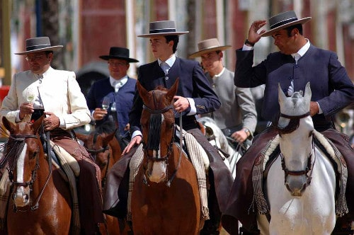 men in straight brim fedoras and suits riding horses