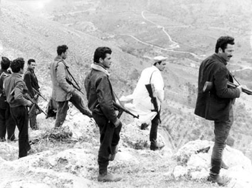 vintage men with machine guns standing on hill overlooking sicily italy