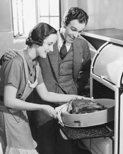Vintage wife putting roast in oven husband looking on.