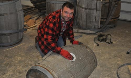 Sanding a whiskey barrel.