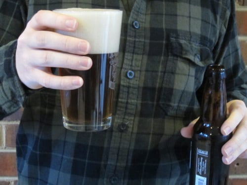 Man pouring beer into pint glass.