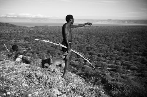 Young boy standing with spear hunting gear and a dog..
