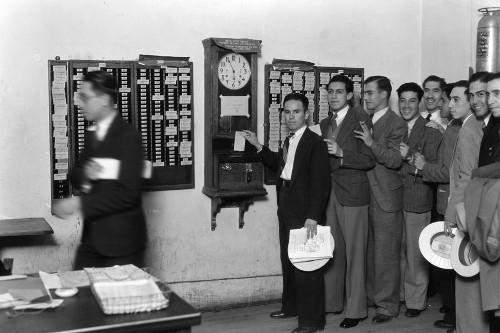 Vintage IBM office workings clocking in suits in line.