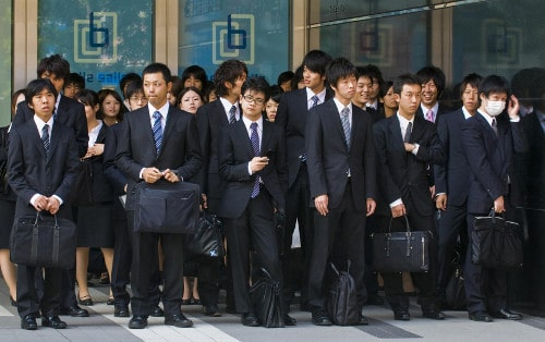 Vintage japanese students are standing and holding bags.