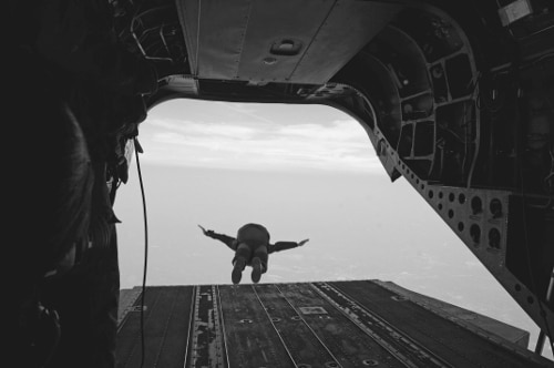 vintage soldier paratropper jumping out of back of airplane