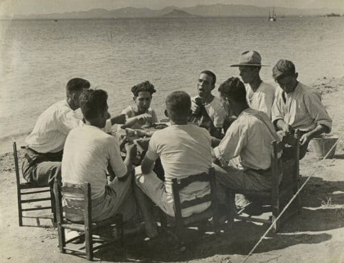 Vintage men eating around dinner table on beach ocean.