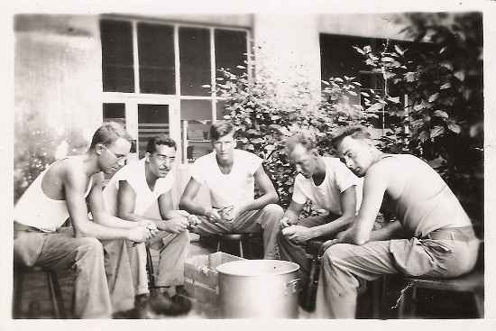 vintage men sitting around white tees whittling
