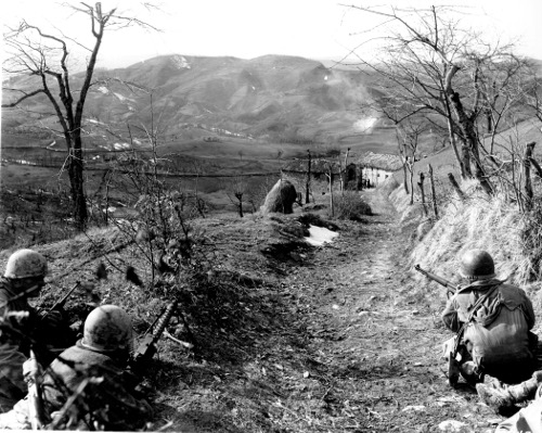 Vintage men military soldiers crouching trail on mountain with there guns.