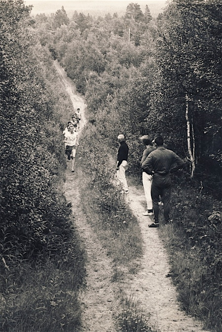 vintage runners trail running through forest