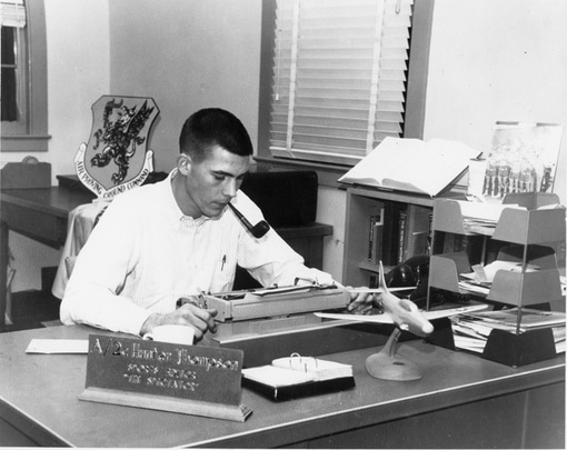 Young hunters thompson writing on typewriter at desk with tobacco pipe in his mouth.