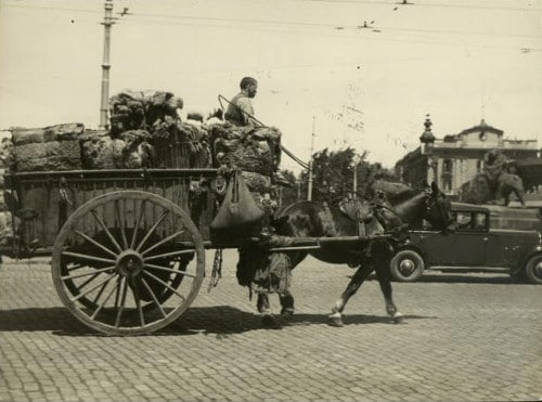 Vintage man in carriage horse pulled wagon full of things.