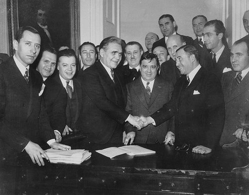 vintage men suits shaking hands big group around behind them