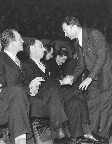 vintage businessman shaking hands with man sitting in arena