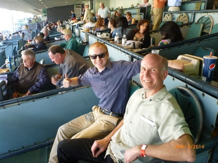 Men giving pose by sitting in horse riding stadium.
