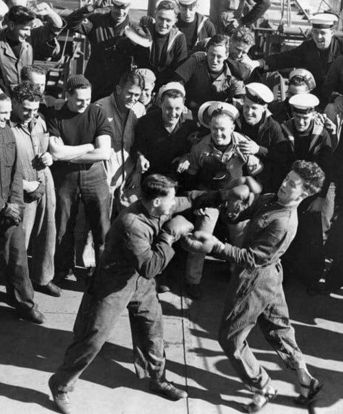 vintage amateur men boxing in street clothes with large group of onlookers