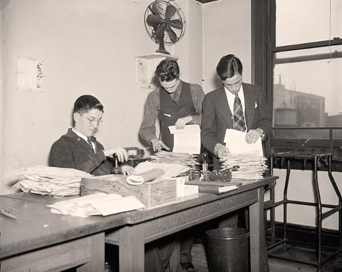 Vintage men sorting papers at table.