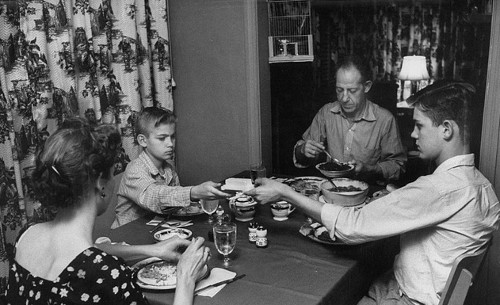 vintage family eating at dinner table brother passing dish to brother