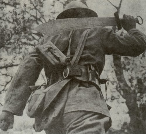 vintage soldier man carrying large machete on shoulder