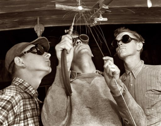 vintage men welding with safety goggles