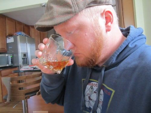 man sniffing whiskey in old fashioned rocks glass