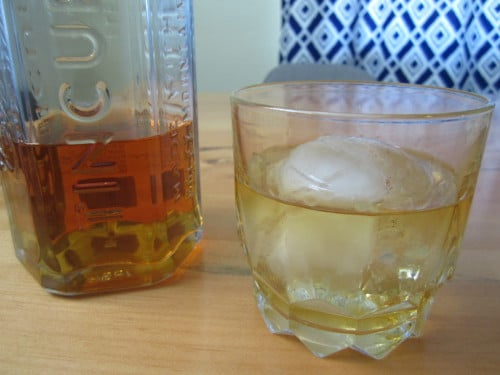 whiskey in glass with large ice ball