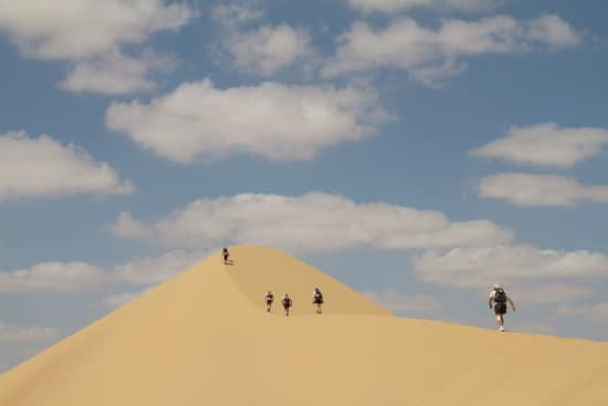 runners in sahara desert ultra marathon running on sand dune ridge