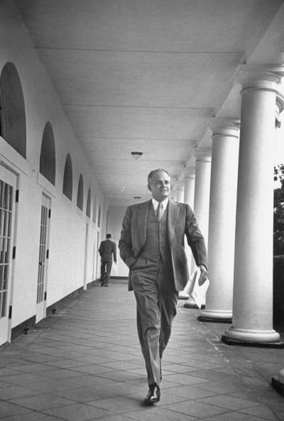 vintage man in suit walking down white house promenade