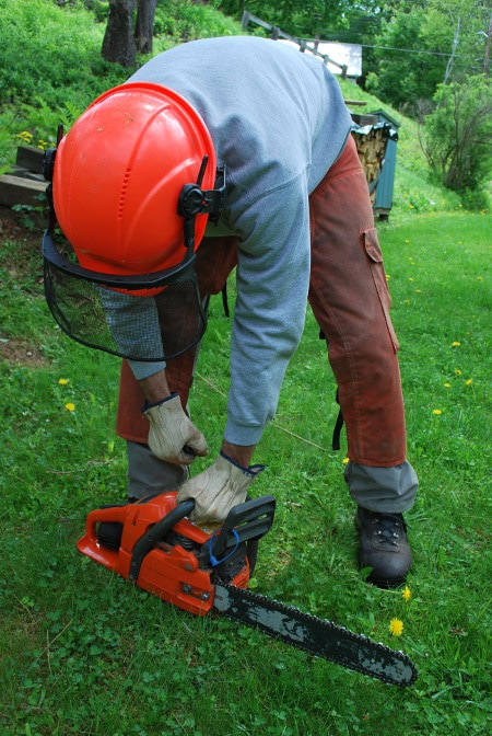 man starting chainsaw safely on ground saw safety