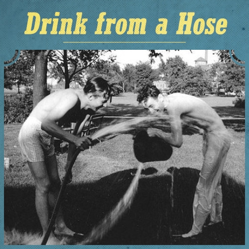 vintage young men drinking water from hose