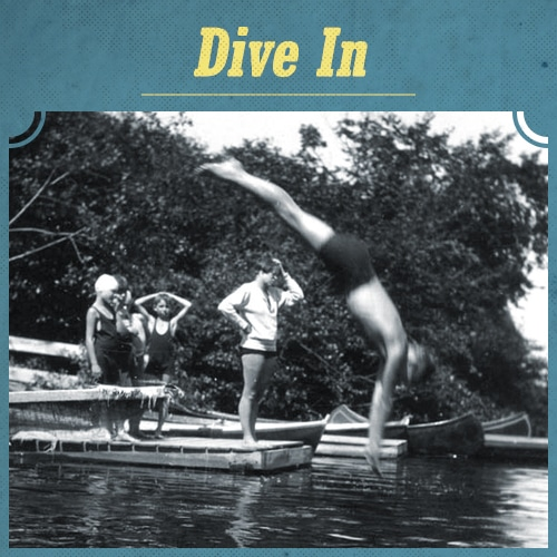 Vintage men diving into river from dock.