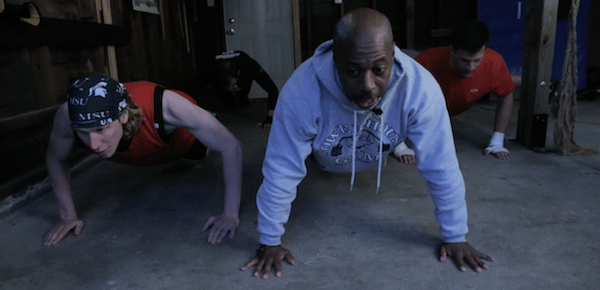 Men in garage doing push ups home fight club.