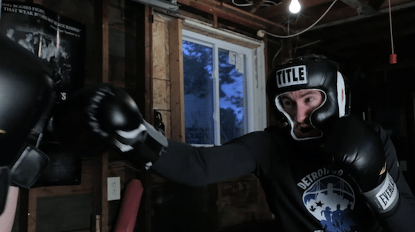 Man in garage boxing gear punching speed bag.