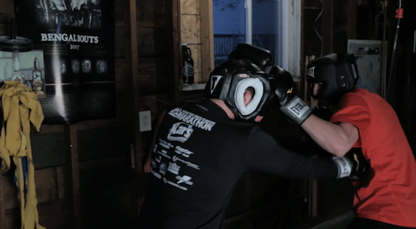 two men fighting sparring in garage home fight club