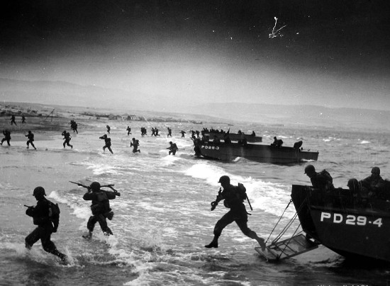 D-day Normandy invasion men running off ships storming beaches.