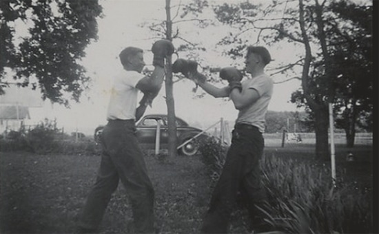 Vintage young man boxing outdoors with boxing gloves.