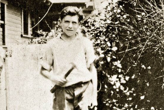 Louis Zamperini as young boy holding hammer in yard