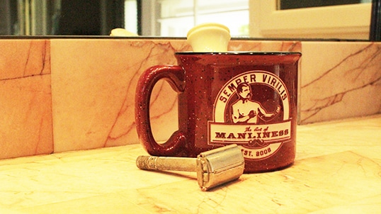 The Art Of Manliness shaving machine and coffee mug placed at table.