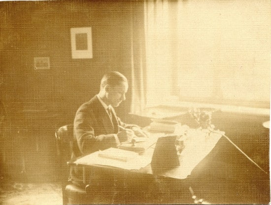 vintage man writing at desk sepia toned light