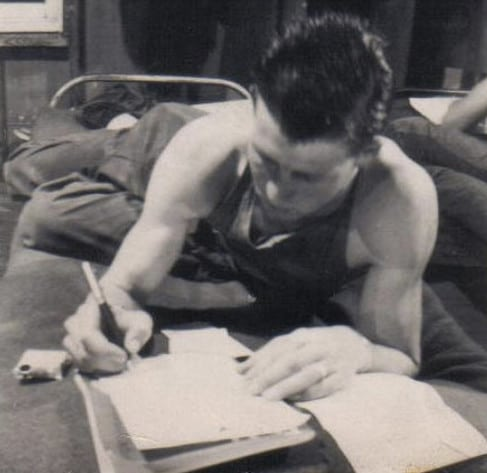 vintage soldier in cot writing letter