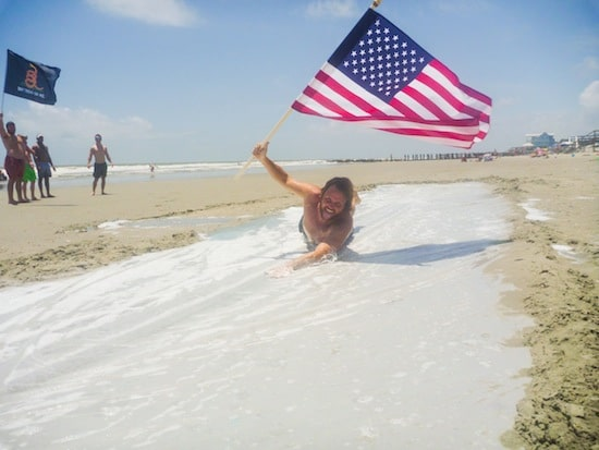 Man sliding on beach with American flag adult slip n slide.