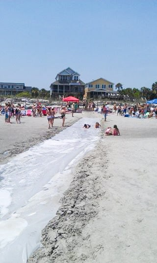 Adult sized mega slip n slide on beach.