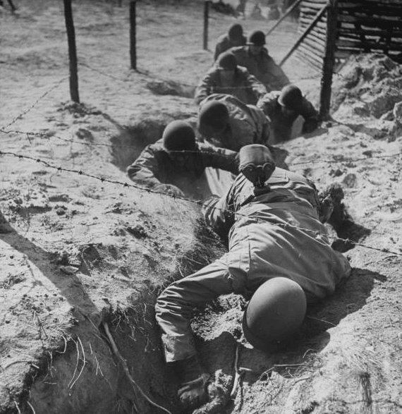vintage soldiers crawling through trench boot camp under barbed wire