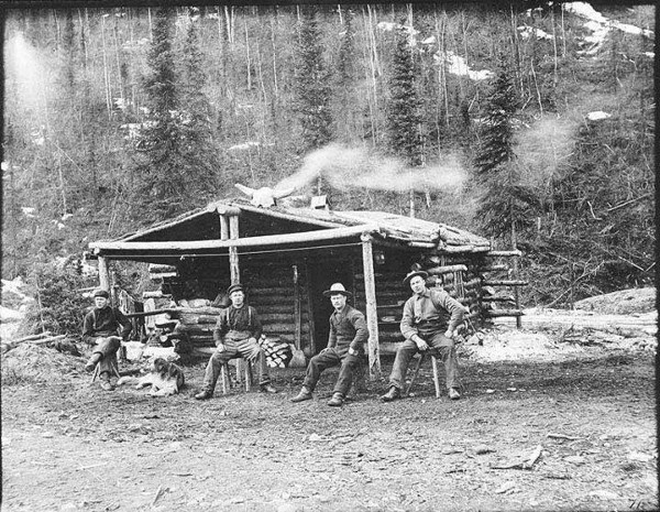 vintage wood log cabin in middle of woods men sitting out front